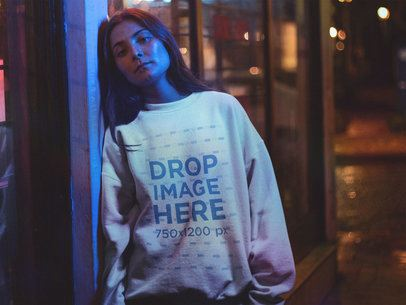 Young Woman Wearing a Crewneck Standing Under a Blue Light at Night a12690