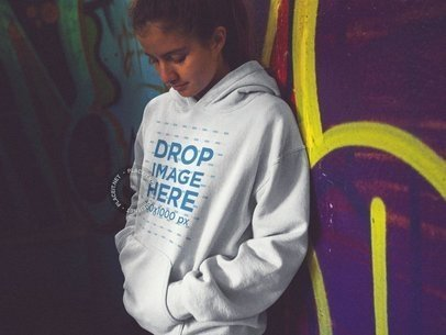 Girl Wearing a Pullover Hoodie Mockup Leaning on a Graffiti Street Wall a12845