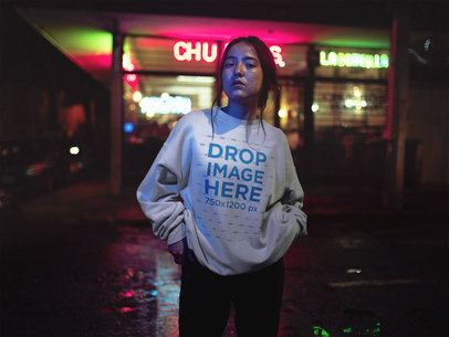 Crewneck Sweatshirt Mockup of a Young Asian Girl in Front of Neon Street Lights a12713