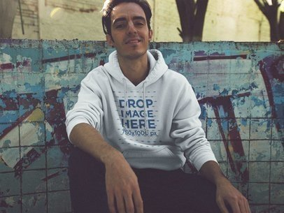 Cool Guy Sitting Against a Graffiti Wall Pullover Hoodie Mockup a12842