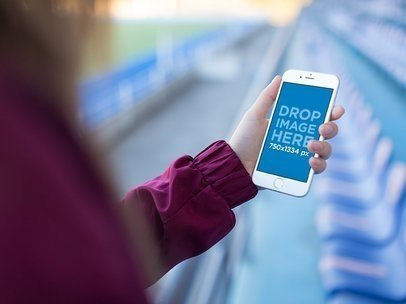 Mockup Template Of A Girl Holding An iPhone While Looking At A Blue Stadium a14090
