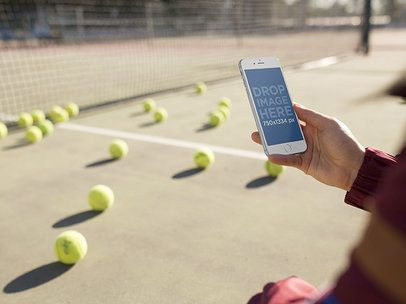 Mockup of a Woman Holding An iPhone in Portrait Position While At A Tennis Court a14092