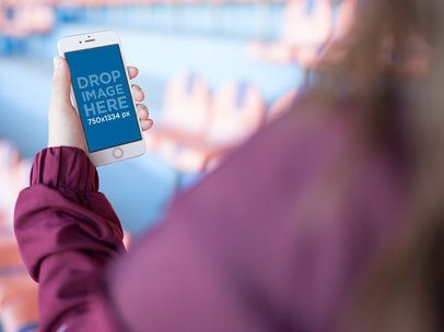 Mockup Of A Girl Using Her White iPhone 6 While At A Red And Blue Stadium a14091