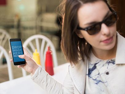 Black iPhone 6 Being Held By Girl With Sunglasses At A Diner Restaurant Mockup a13993