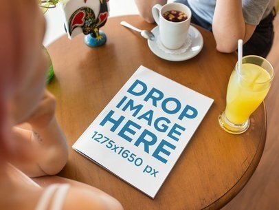 Mockup of a Magazine Lying on a Wooden Table While Two Friends are Gossiping and Having a Drink at a Coffee Shop a14365