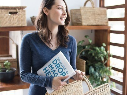 Pretty Woman Holding a Book and a Basket While at the Grocery Store Mockup a14429