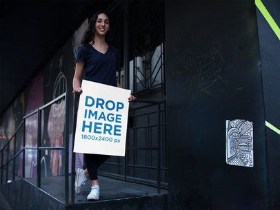 Mockup of a Happy Girl Holding a Poster While in the Street a14470
