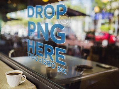 Mockup of a Window Decal With a Coffee Cup on a Table Alongside It a14520