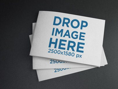Mockup of Three Small Catalogs Stacked on a Black Surface a14586