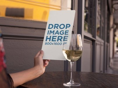 Urban Restaurant Menu Booklet Mockup Held on a Wooden Table With a Glass of White Wine a14769