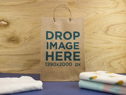 Paper Bag Standing Near T-Shirts Against a Wooden Background a14708