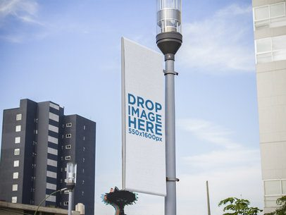Mockup of a Vertical Banner Hanging from a Light Pole in the City a15166