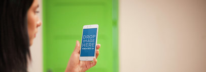 iPhone 6 Mockup Featuring a Brunette Woman Against a Green Backdrop a3041wide